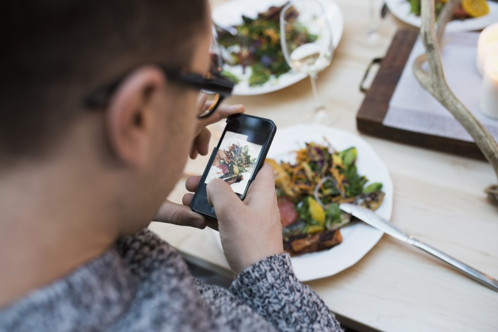 Man photographing plate of food at restaurant table